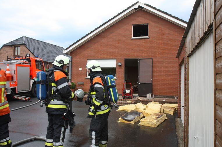 Enkele brandweermannen maken zich op voor warmtemetingen in de woning van Johny Vanacker, met op de achtergrond de verschroeide isolatie.