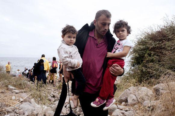 Een vader met zijn twee kinderen na hun aankomst op het Griekse eiland Lesbos.