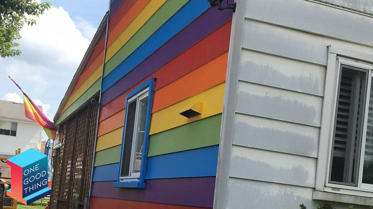 Lesbisch koppel schildert zijgevel in regenboogvlag na pesterijen.