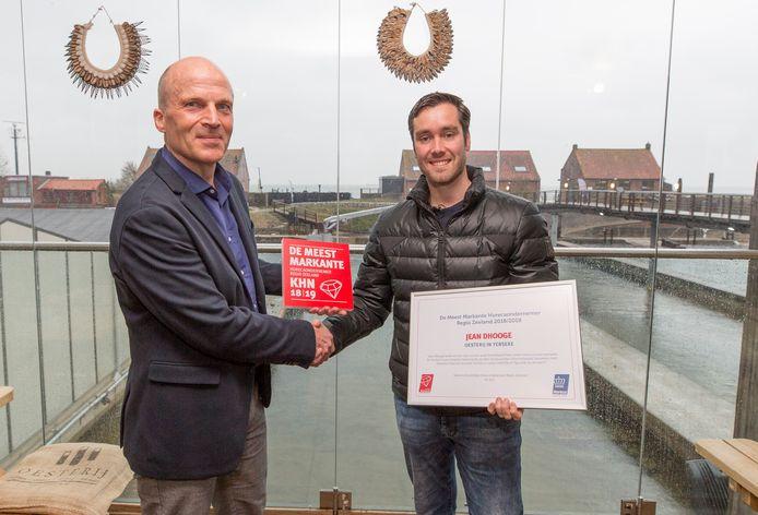Jacco de Lignie van KHN afdeling Zeeland overhandigt de prijs en de bijbehorende oorkonde aan Jean Dhooge van de Oesterij in Yerseke.