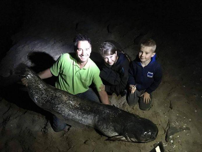 Jelle Grintjes met zijn dochter en zoon en de meerval die hij zaterdag ving.