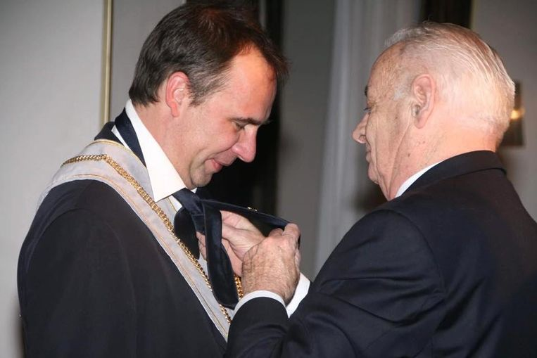 André Vandenbogaerde knoopt de das van burgemeester Benoit tijdens diens aanstelling bij de Orde van de Ezel.