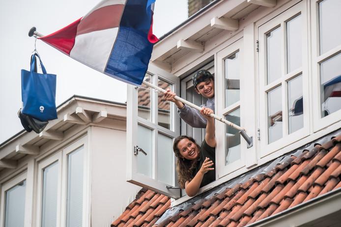 Geslaagd! Luba en Mats plaatsen de vlag met hun schooltassen met vereende krachten in de houder bij het dakkapel.