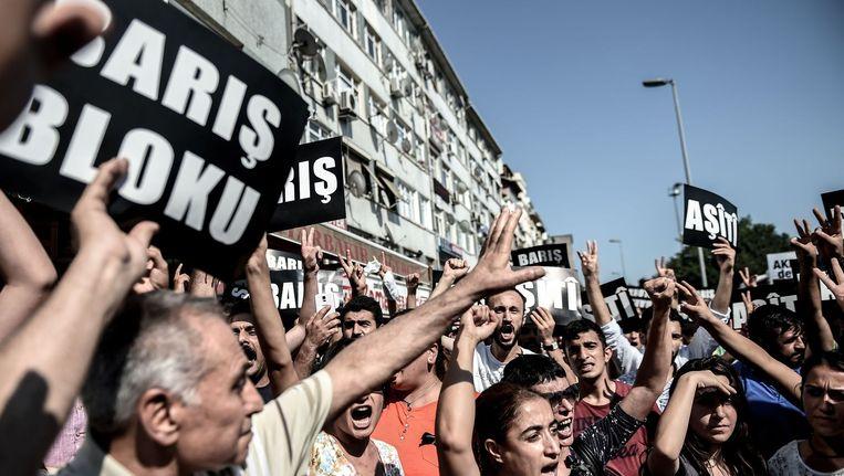 De Turken organiseerden zondag een vredesmars in Istanbul als reactie op de oplopende spanmingen tussen de Turkse regering en de PKK. Op hun borden is het woord 'vrede' te lezen. Beeld afp