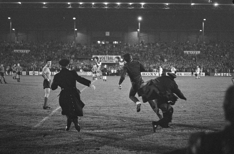 Na de thuiswedstrijd bestormen uitzinnige Ajaxsupporters het veld en weten ze de agenten op het verkeerde been te zetten. Beeld Nationaal Archief/Anefo 921-7324