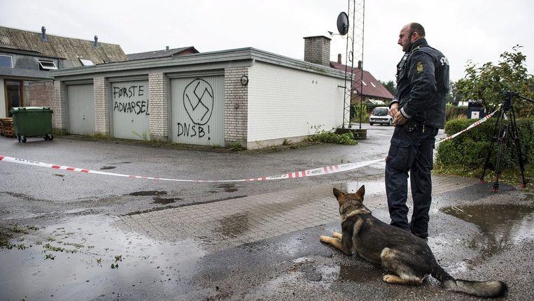 Een agent staat op wacht bij een asielzoekerscentrum, dat is beklad door neonazi's, in het Deense Trustrup. Beeld reuters