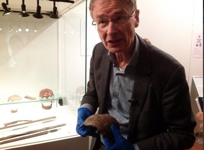 Archeoloog Nico Roymans toont een schedel die tijdens de veldslag van Caesar met een Romeinse werpspeer is doorboord.