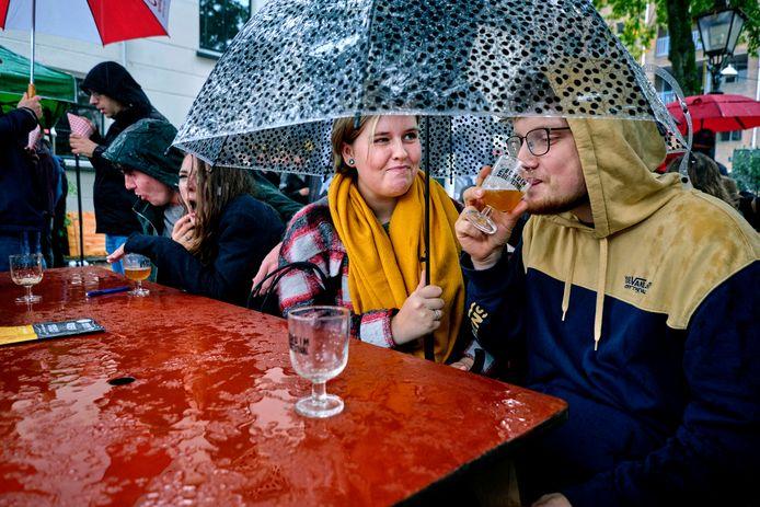 Door het slechte weer genoten de bezoekers van bierfestival Schuim in Dordrecht onder de paraplu van de verschillende biertjes.