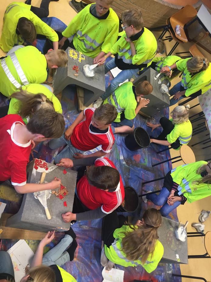 Leerlingen van groep 8 van de katholieke basisschool Op Weg uit Haarle versieren zitelementen die voor het schoolplein zijn bedoeld.