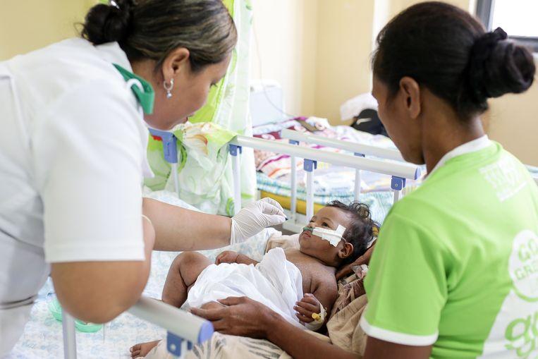 Een meisje met mazelen krijgt vitamine-a toegediend in een ziekenhuis op Samoa. Beeld AFP