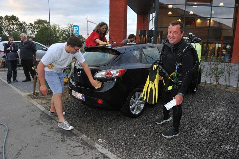 Leden van de duik- en petanqueclub wassen auto's om hun lokalen af te kunnen werken.