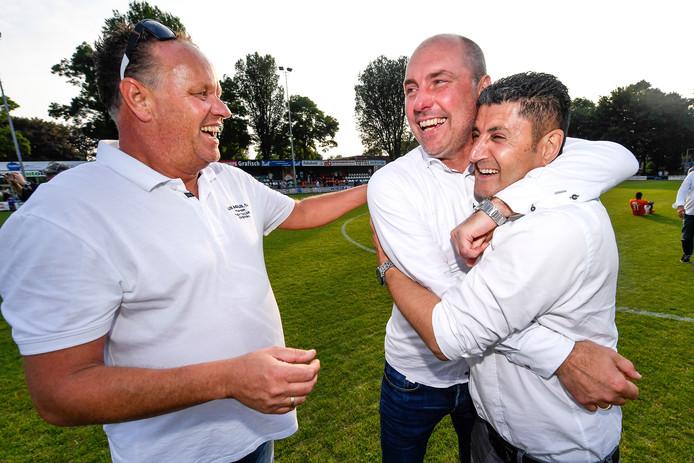 Coach John Blok (midden) viert de promotie van Scheveningen met sponsoren.
