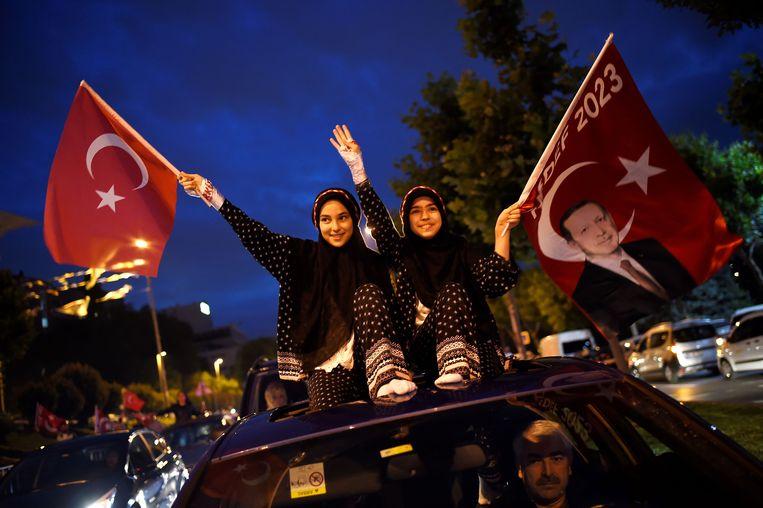 Vrouwen zwaaien met de Turkse vlag en met een vlag waarop Erdogan staat afgebeeld.