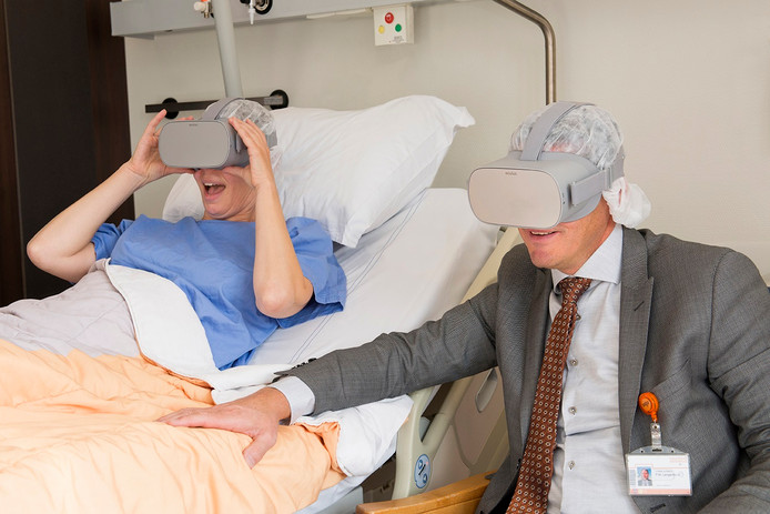 Een patiënt en Peter Langenbach (r) proberen de brillen uit.