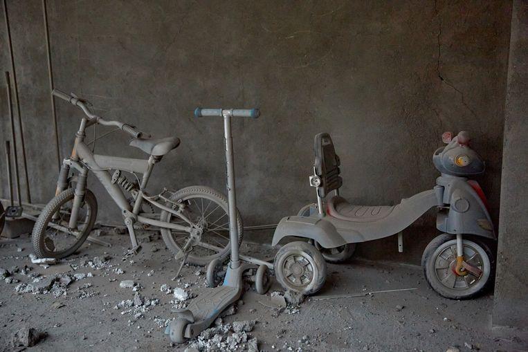 Stilleven met driewieler, step en kinder-BMX in Stepanakert. Voor het donkergrijze, alles bedekkende gruis dat volgt op de bommen is elke leeftijdscategorie gelijk. Beeld Alex McBride/ Getty Images
