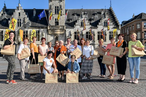 Vrouw & Maatschappij op de Grote Markt met hun tassen.