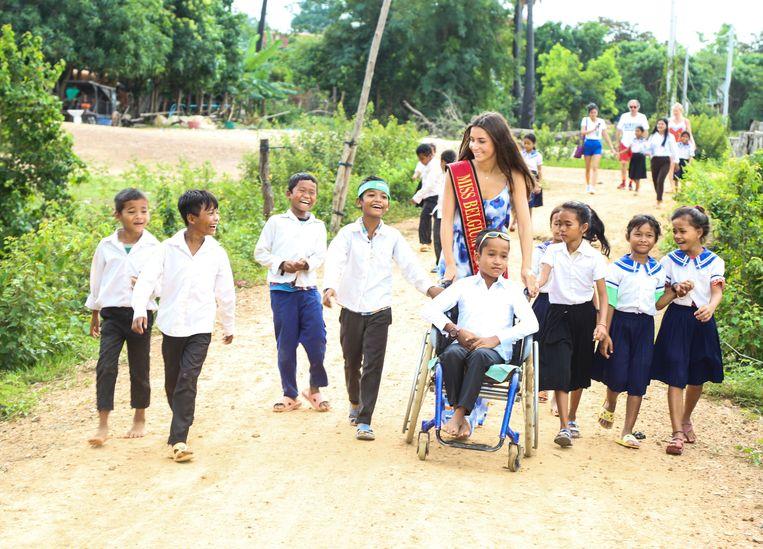 Miss België helpt een kindje met spina bifida, die gedeeltelijk verlamd is, met aankleden en neemt hem in zijn rolstoel mee naar school.