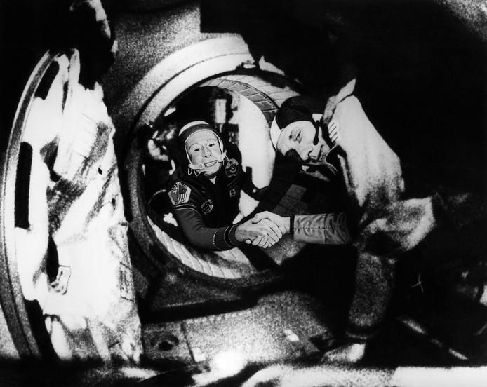 Aleksej Leonov (links) in juli 1975. Hij schudt de hand van de Amerikaan Thomas Stafford na de geslaagde koppeling van beide ruimtevaartuigen.