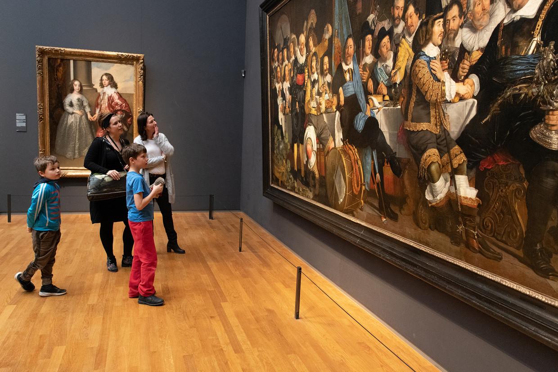 Thomas (rode broek) kijkt met zijn moeder Juliette Tesselhoff (witte trui), broer en de rondleider van Rijksmuseum naar schilderijen tijdens 'prikkelarme avondopenstelling'. Beeld Myra May