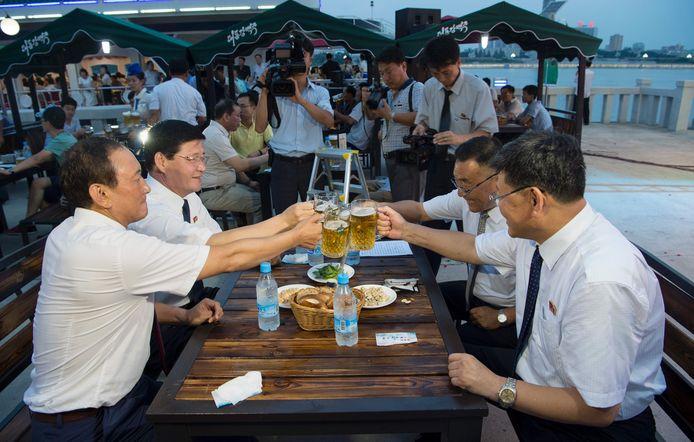 Choe Yong Nam (L) en andere Noord-Koreaanse ambtenaren proosten tijdens het bierfestival.
