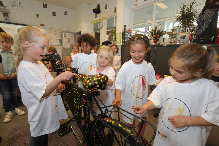 Kinderen schilderen enkele fietsen voor het WK cyclocross.