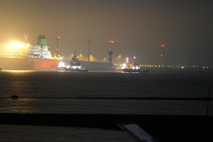 De tanker wordt weggetrokken door sleepboten.