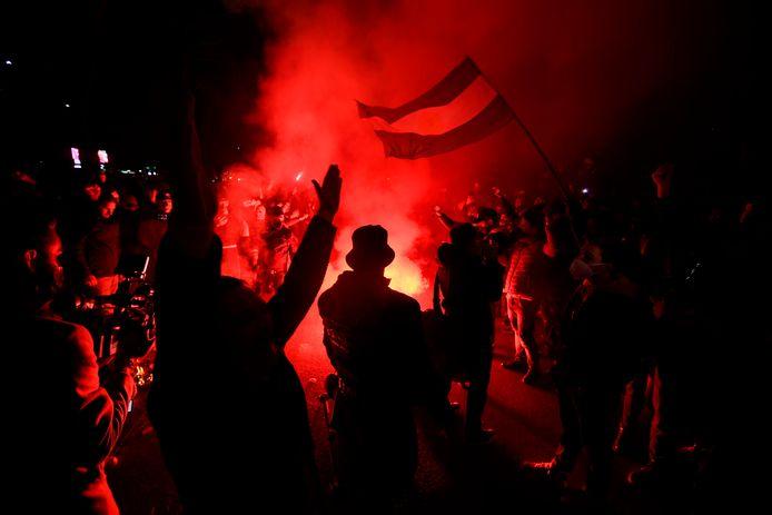 Fans steken fakkels af om Maradona te eren bij stadion San Paolo.