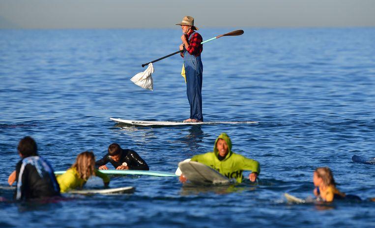 De surfpakken werden zaterdag in Newport Beach ingeruild voor verkleedkleren. In die kustplaats in de Amerikaanse staat Californië werd het jaarlijkse Halloweensurffeest gehouden. De rest van Amerika moet nog tot donderdag wachten met verkleden, dan is het écht Halloween.   Beeld AFP