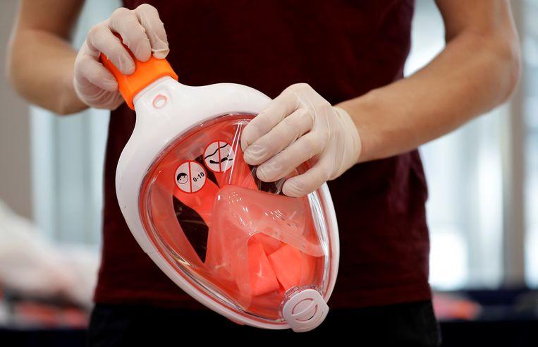 In een aantal landen wordt het snorkelmasker van Decathlon door zorgpersoneel gebruikt als bescherming tegen het coronavirus. In sommige landen, zoals in Nederland bij de Universiteit Twente, proberen onderzoekers het nu ook geschikt te maken voor de ondersteuning van de ademhaling van coronapatiënten. Beeld REUTERS