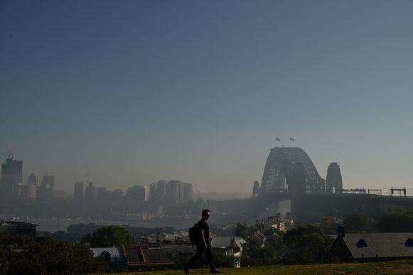 De Sydney Harbour Bridge met op de achtergrond de stad onder een deken van rook.