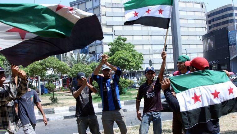Jonge mannen in het naburige Libanon zwaaien met Syrische vlaggen van voor het regime van Assad. Beeld afp