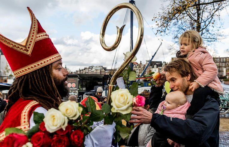 De Nieuwe Sint deelt ook dit jaar weer bloemen uit aan Amsterdammers en viert op 25 november feest op het Museumplein. Beeld ANP