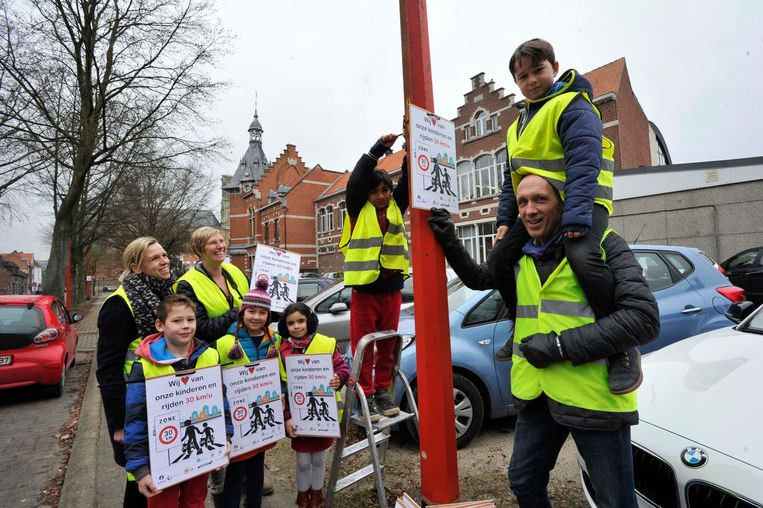 De leerlingen van het derde jaar hangen bordjes op langs de straat aan hun school.
