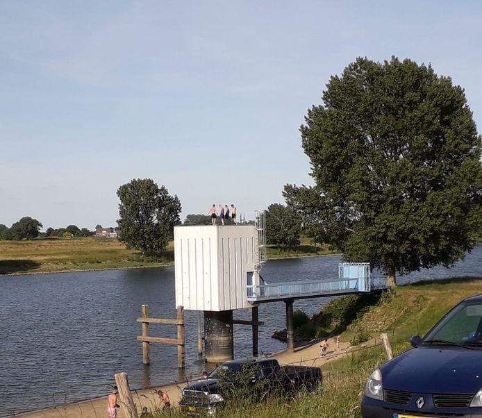 Hoog bovenop het peilhuisje aan de Maas in Lith hebben vier jongens pret.