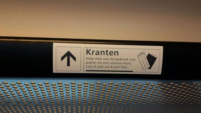 Stickers roepen reizigers op om hun krant in de speciaal daarvoor bestemde bagagerekken te laten liggen. Foto: NS