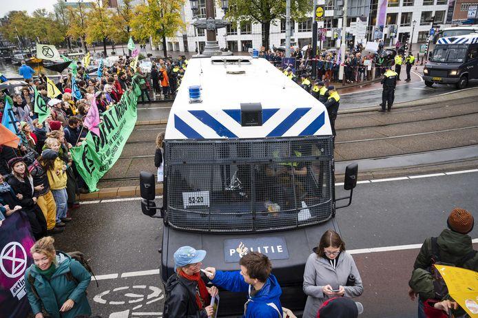 Demonstranten van Extinction Rebellion blokkeren de Blauwbrug in Amsterdam. Actievoerders die de brug niet wilden verlaten zijn gearresteerd door de politie.