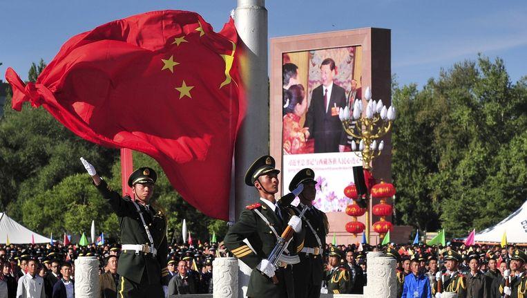 Chinese vlag wordt gehesen bij de viering van 50 jaar Tibetaanse Autonome Regio, 8 september. Beeld reuters