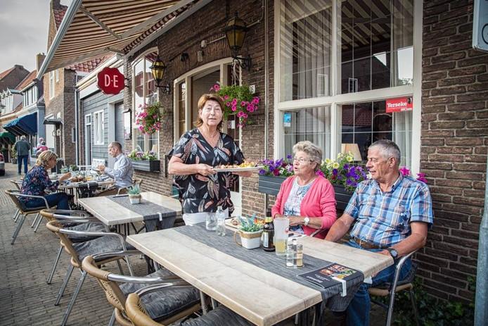 Eigenaresse Ankie Petersen bedient gasten op het terras van 't Hoekje van Yerseke.