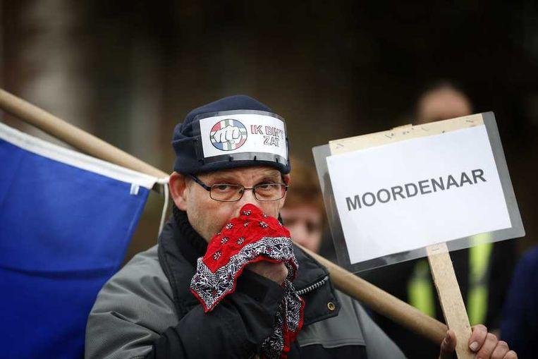 Een demonstrant houdt symbolisch een doekje tegen zijn neus tegen het bloeden. Daarmee uit hij zijn ongenoegen tegen het in zijn ogen lage bedrag dat het kabinet uittrekt ter compensatie van de aarbevingslachtoffers. Beeld anp