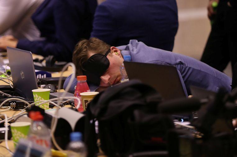 Wachtend op de uitslag van een nachtelijke vergadermarathon in Brussel doet een journalist een dutje. Beeld Reuters