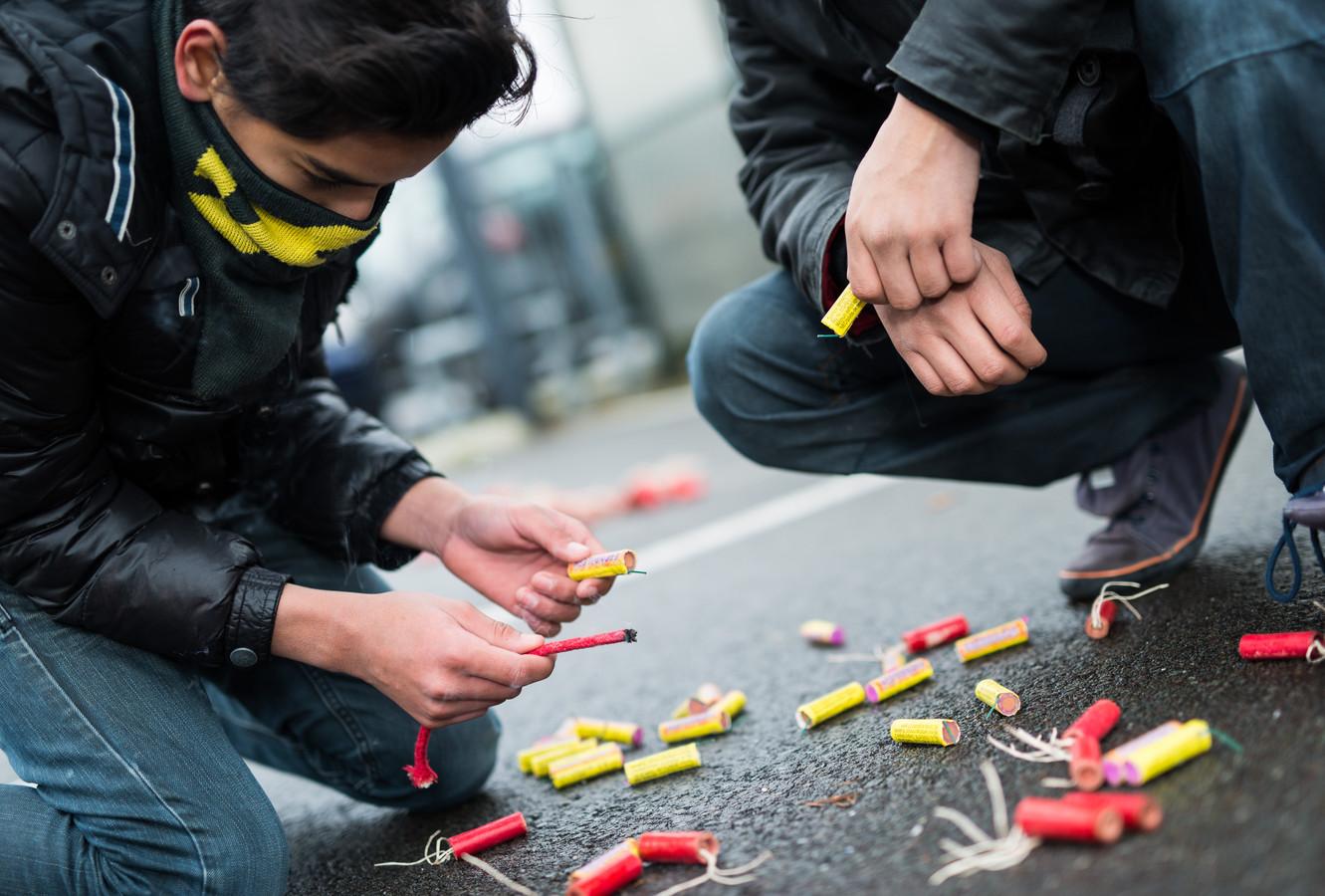Een jongen steekt vuurwerk af op straat.