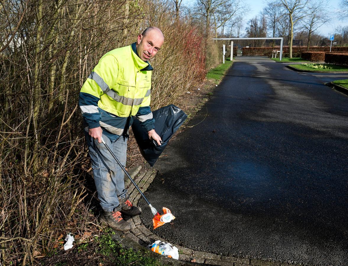 Een medewerker van het onderhoudsteam van begraafplaats De Rijnhof ruimt elke ochtend de troep op van het parkeerterrein.