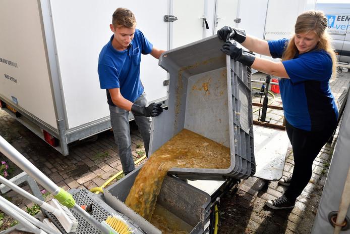 Verslaggever Rachel van Kommer maakt samen met Dennis van Wolfswinkel (links) de septic tank vol poep, plas en wc-papier schoon.