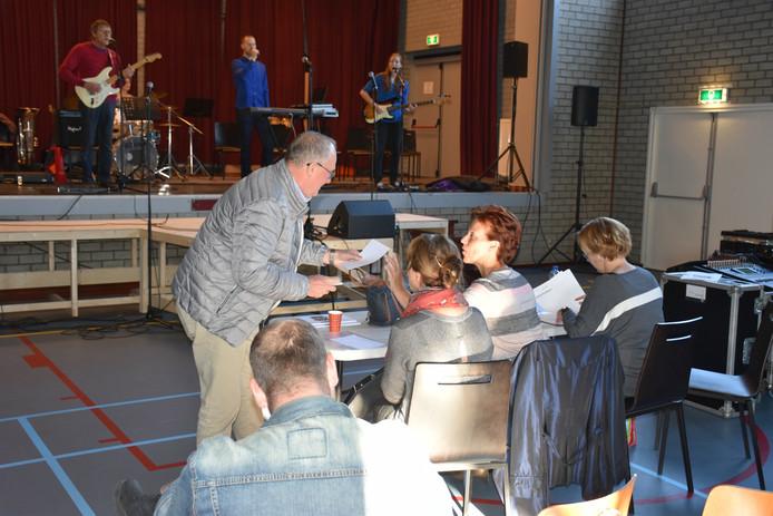 Theo Raijmakers reikt Maria van Asseldonk actuele informatie voor Sing Swing aan.