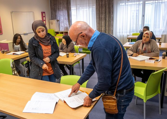 Jan van Heese geeft cursiste Ashrak (links) uitleg bij een taalles bij Taalonderwijs Dunya.