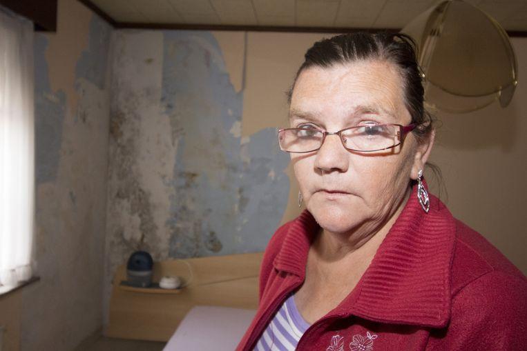 Wivina Borremans in haar slaapkamer in het huurhuis. De schimmel en beschadigingen zijn duidelijk te zien.