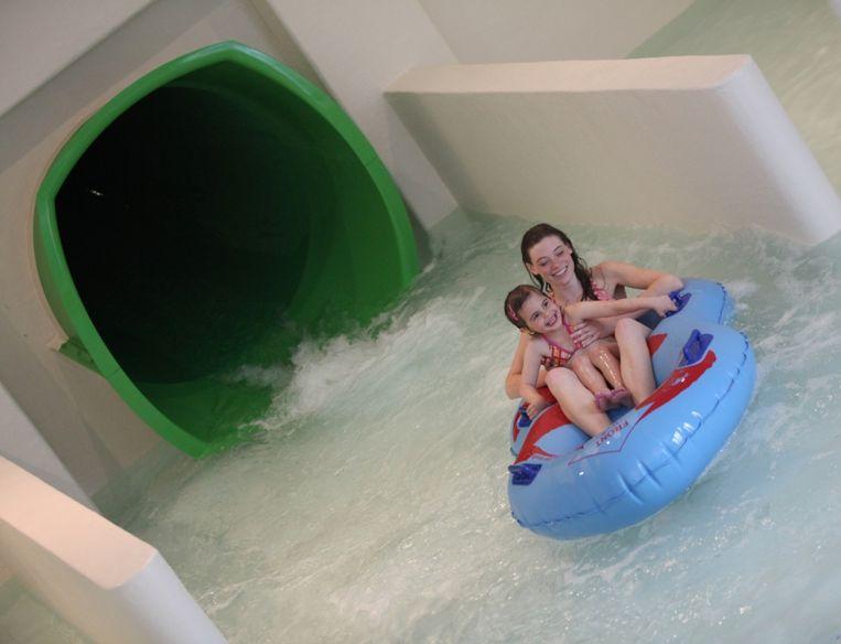 Twee meisjes glijden met een zwemband uit de waterglijbaan.