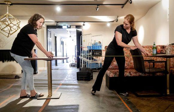 Een café in Den Haag: medewerkers meten de afstand tussen de tafels.