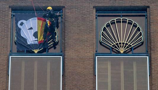 Actievoerders van Greenpeace hangen een vlag op bij het hoofdkantoor van Shell.