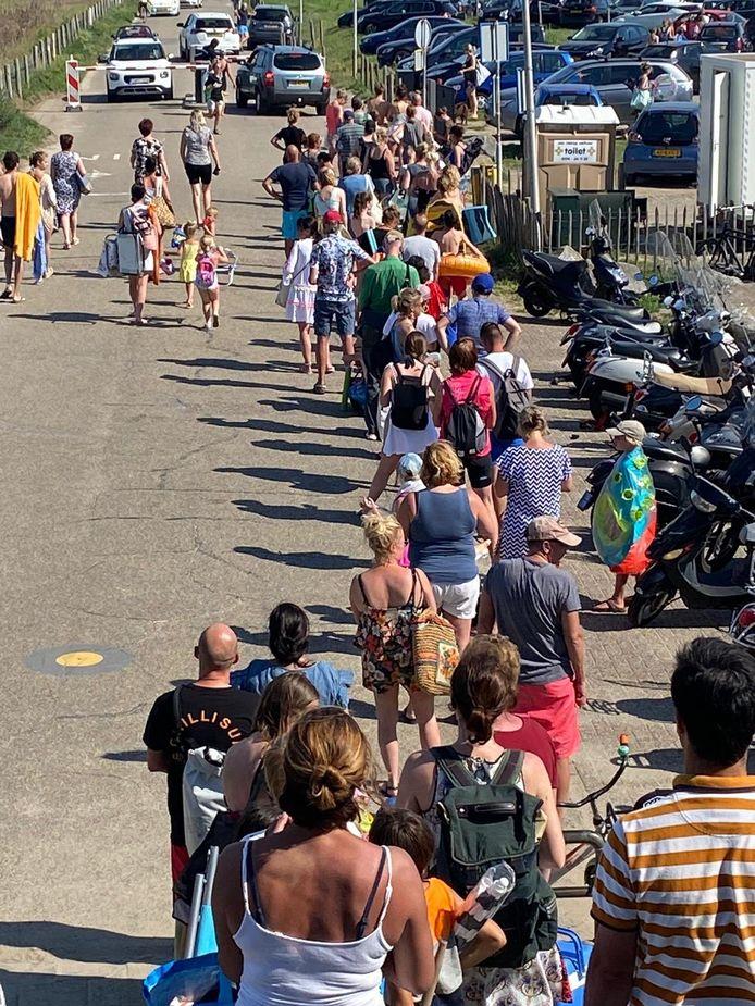Een enorme rij van wachtende mensen bij de parkeerautomaat bij het strand van Molenslag in Monster.